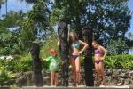 dzieciaki przy rzeźbach z pni palmowych