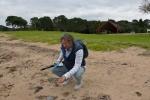 Mariusz przesiewa piasek na plaży, z której wyruszają w morze pirogi maoryskie
